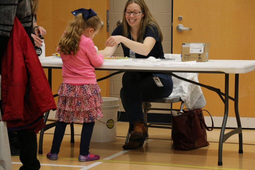 Table With Child Interacting And Employer Smiling